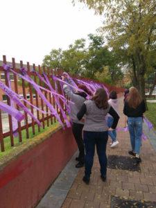 Un grupo de personas poniendo lazos lila en una valla de un colegio