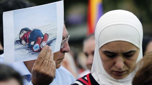 Imagen de inmigrantes con una foto del niño ahogado
