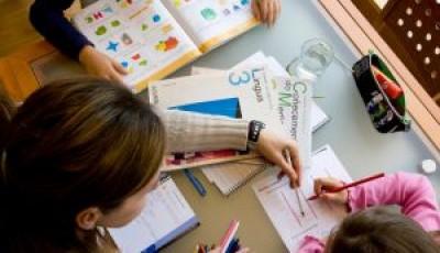 Imagen de unos niños estudiando en una mesa con libros
