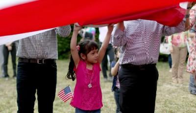 Imagen de una niña inmigrante ayudando a desplegar una bandera