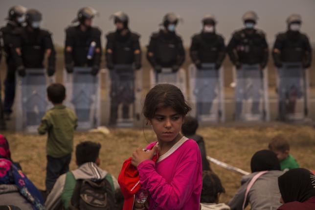 Una joven refugiada y policías al fondo