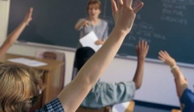Imagen de una clase con niños levantando la mano