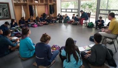 Imagen de un grupo dando clase sentados en el suelo en círculo