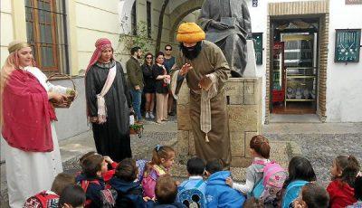 Imagen de alumnos y actores vestidos de árabes ante una estatua
