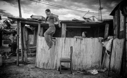 Imagen de una joven saltando ante una chabola