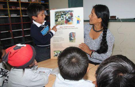 Imagen de una maestra y un alumno indígenas