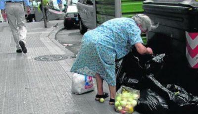 Foto de una señora mayor buscando en la basura