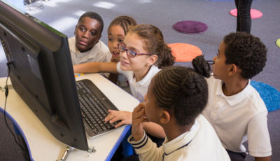 imagen de varios niños viendo un ordenador