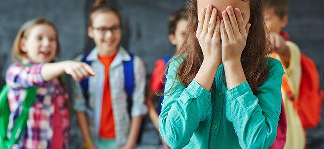 varias niñas se ríen de otra que se tapa la cara