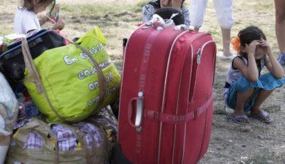 imagen de una mujer llorando con unas maletas y dos niñas