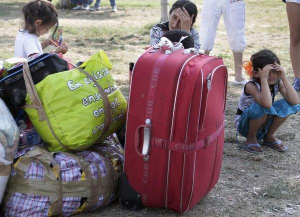 imagen de una mujer preocupada con unas maletas y varios niños