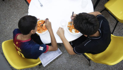 imagen de dos niños comiendo en una mesa