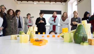 un grupo de personas ante una mesa con figuras hechas con fruta