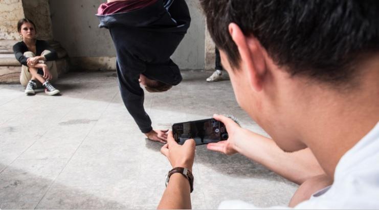 un joven graba en vídeo a otro que hace acrobacias