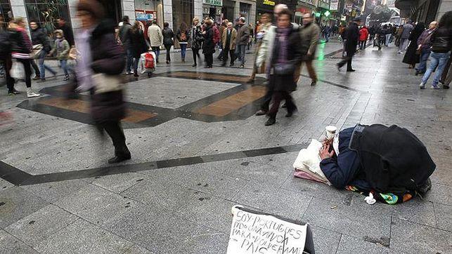 Imagen de una persona pidiendo en una calle de ciudad