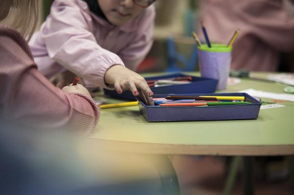 imagen de dos niños/s en una mesa con lápices de colores