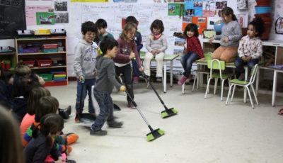 niños y niñas barriendo un aula