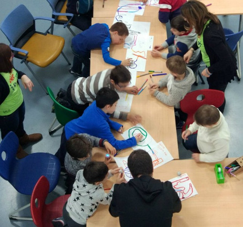 imagen de varios niños en una mesa dibujando con una profesora