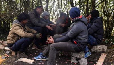 imagen de un grupo de inmigrantes calentándose en un fuego en Calais