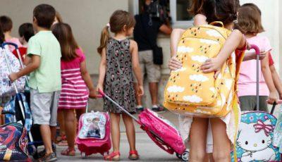 varios niños y niñas en la puerta de un colegio