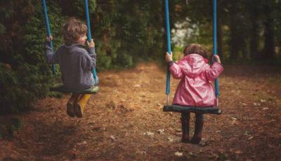 una pareja de niños/as en unos columpios