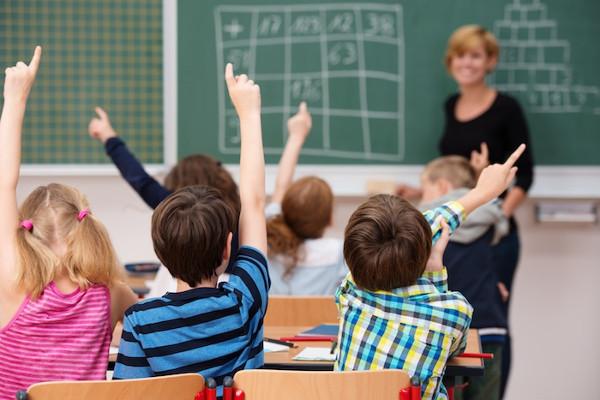 grupo de alumnos con manos alzadas en una clase