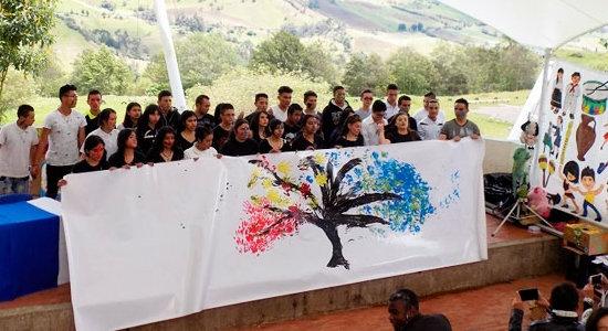 Imagen de un grupo de alumnos de una escuela con un cartel pintado por ellos