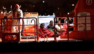 un grupo de inmigrantes en la cubierta de un barco de noche