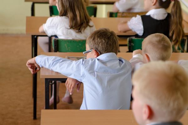 imagen de un niño rubio con gafas en una mesa de clase