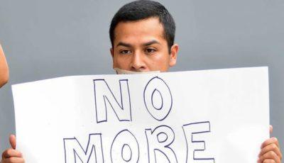 imagen de un joven hispano con la boca tapada con cinta y una pancarta (no más)
