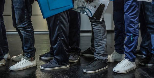 imagen de las piernas de varias personas en una cola para pedir trabajo