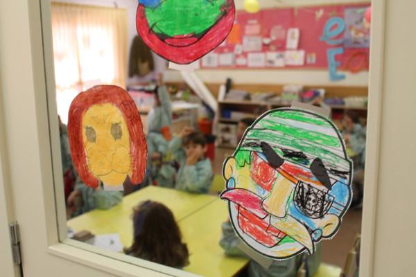 imagen de dibujos infantiles pegados en un espejo de un aula