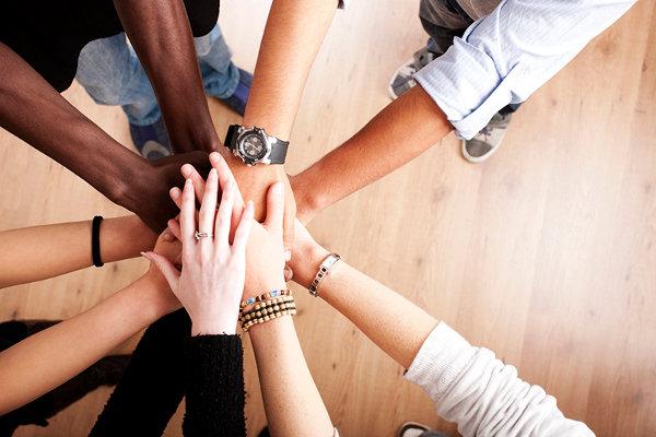 personas con diferentes tonos de piel unen sus manos