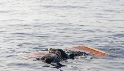 cadáver de una mujer inmigrante sobre una tabla en el mar