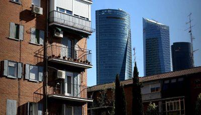 imagen de contraste entre un bloque de pisos del distrito de Fuencarral y las lujosas 4 Torres