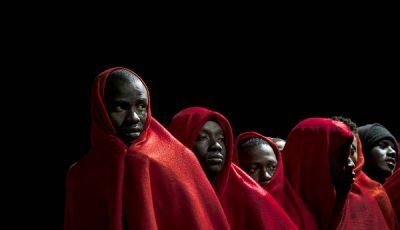imagen de un grupo de inmigrantes de color tapados con mantas rojas