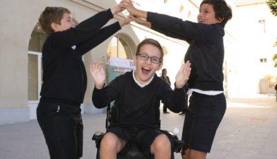 tres niños, uno de ellos en silla de ruedas, juegan en un patio