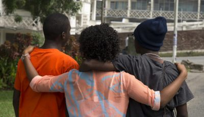 imagen de tres jóvenes de color de espaldas abrazados