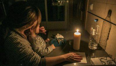 imagen de una madre con un hijo/a alumbrándose con una vela
