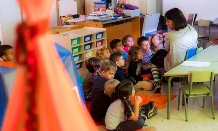 Imagen de una maestra con un grupo de niños/as de infantil