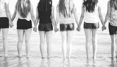un grupo de mujeres blancas de espaldas cogidas de la mano en la orilla del mar