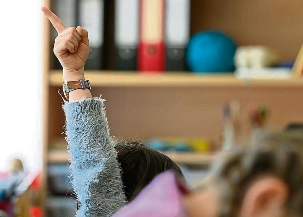 imagen de la mano alzada de un alumno en una clase