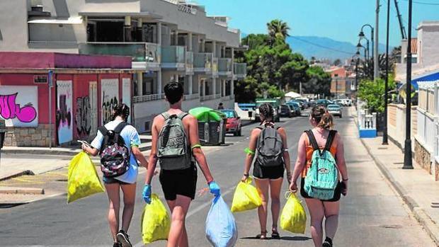 varios jóvenes con bolsas de basura