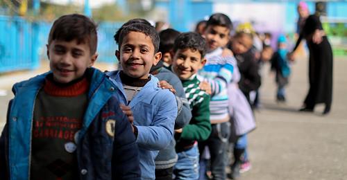 niños extranjeros en una fila para entrar en clase