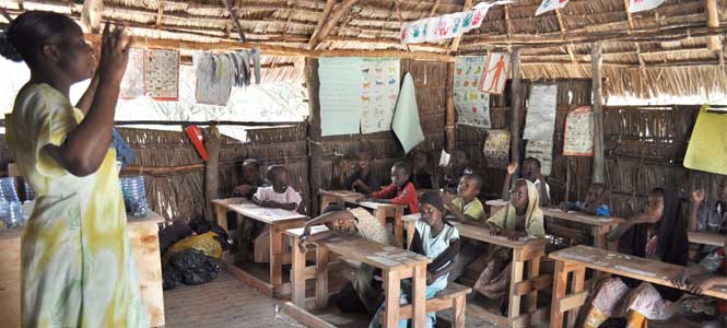 Una maestra da clase en un aula africana