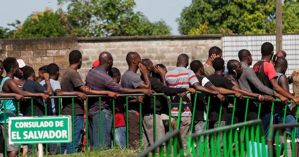 Una larga fila de personas espera para entrar en el Consulado de El Salvador