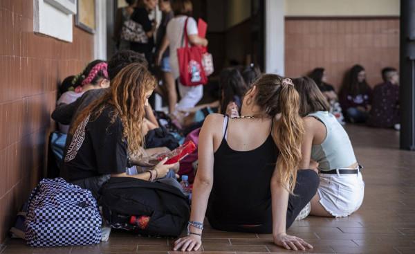 un grupo de alumnas sentadas en el suelo en la entrada de un Instituto