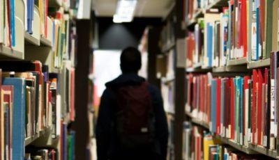 un joven con mochila rodeado de estanterías con libros