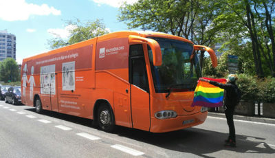 Imagen de una activista con una bandera arcoiris delante del Bus de Hazte Oir