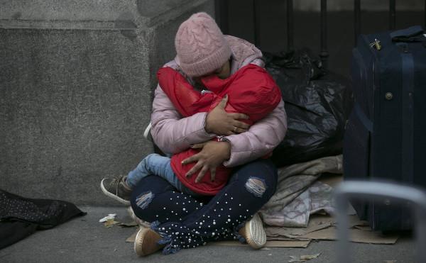 una mujer con un niño en la calle a las puertas del Samur Social de Madrid